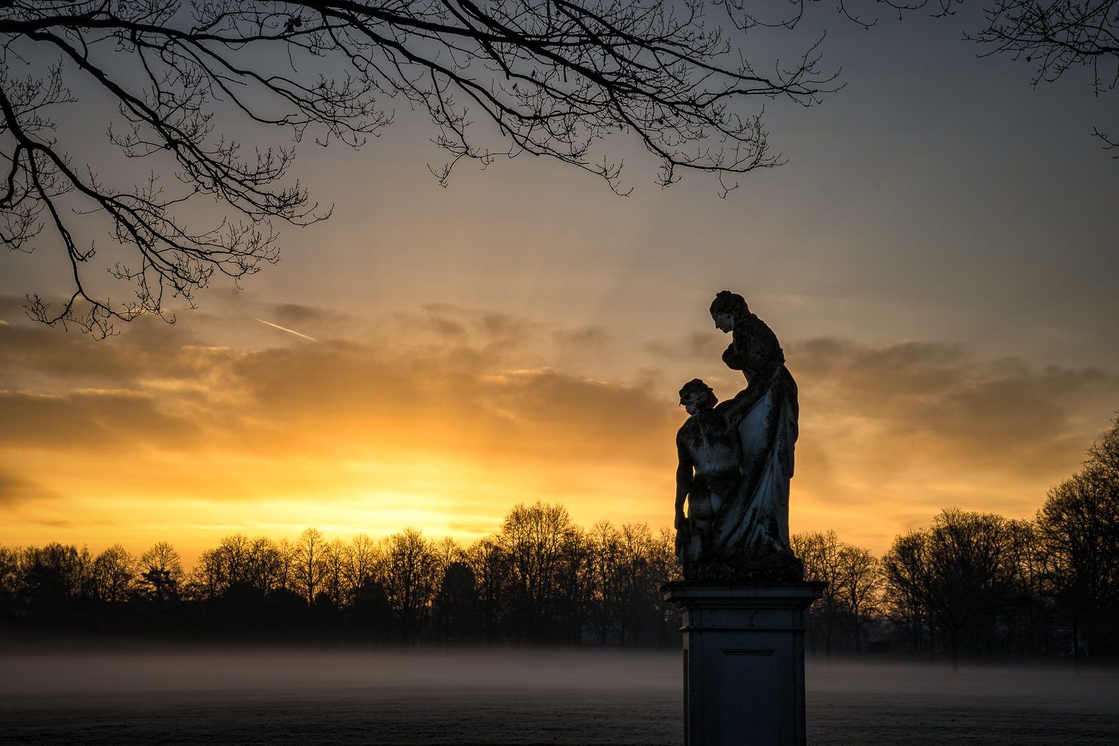 Orangerie Kassel - Fog with a burning sky...  Every month has its uniqueness in each region. Maybe in winter you don't have broad daylight or blue skies, but you have great sunrises with fog. This photo shows a statue from our park in Kassel, the Caritas Romana. At first I thought their story is about a love couple, and so the photo had a very romantiv touch with this burning sky. But then i read about the story of the Caritas Romana and it was about a woman who visited her father every day in the catacombs of the roman empire left to die without bread or water. She gave him to eat from her breast so he could survive, when the romans discovered her they were so overwhelmed by the story that they let him free. So now you can decide if this photo has a romantic touch or not :)  If you want to follow my other voyages in photography at Instagram, please check my other feeds :)  Cosplay Photography: @dont_fade_away_photography_cos  People & Portraits (my new one): @dont_fade_away_photography_ppl